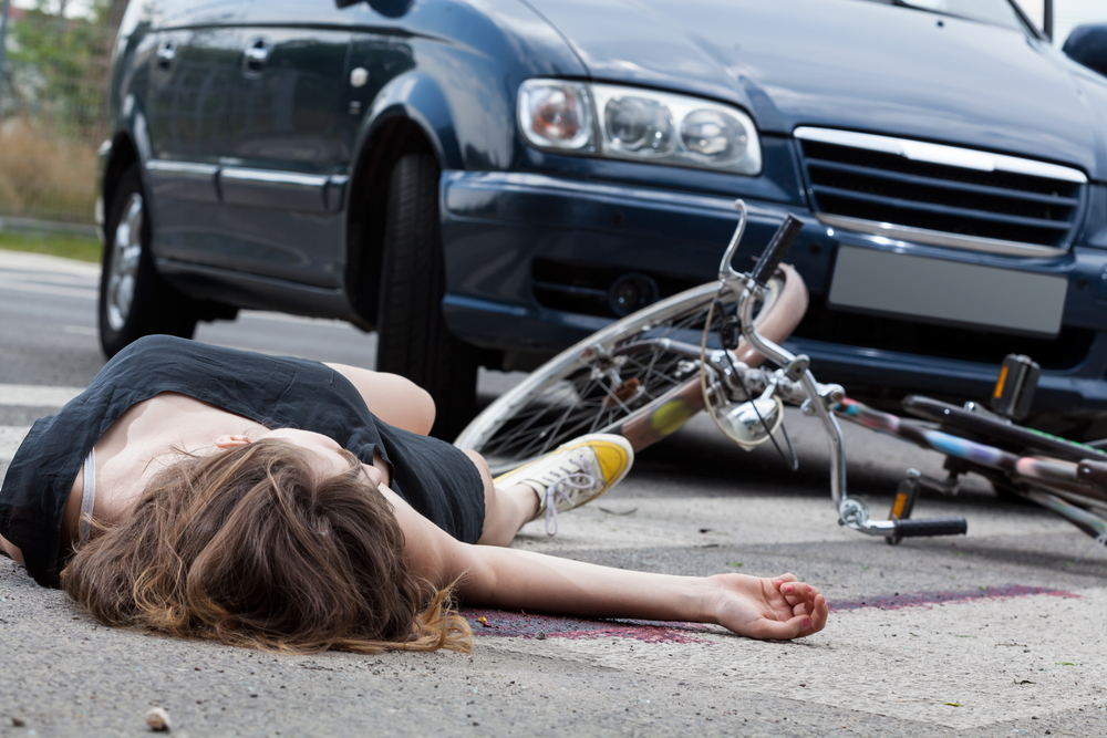 dead female cyclist lying on street after road accident